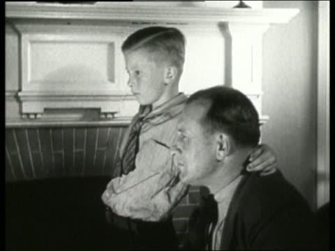 B/W 1930's close up of man and boy / man nods head / listening to radio / NO SOUND