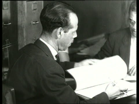 B/W 1930's close up of man looking thru book in office / SOUND