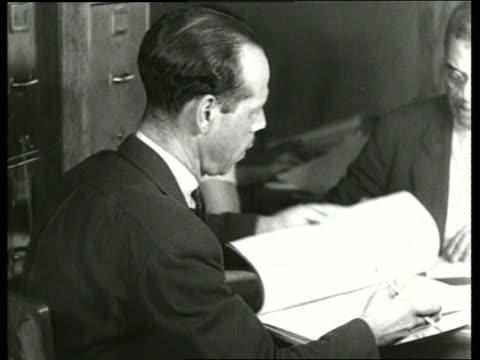 b/w 1930's close up of man looking thru book in office / sound - solo uomini di età media video stock e b–roll