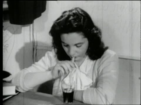 B/W 1950's close up of teen girl drinking soda with straw / Looks up and smiles