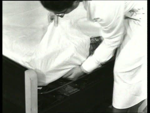 b/w 1930's close up of woman putting sheet on bed / sound - 1935 stock-videos und b-roll-filmmaterial