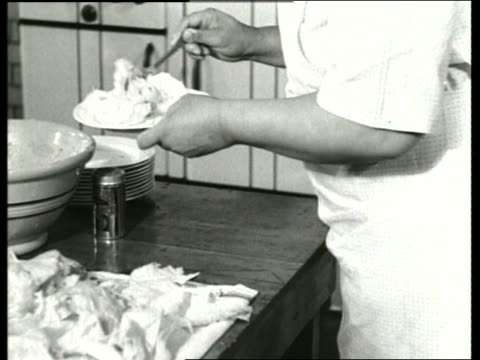 stockvideo's en b-roll-footage met b/w 1930's close up of woman's hands putting food on dish / sound - huishuidkunde