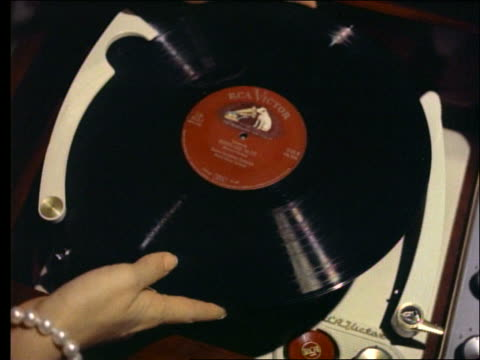 stockvideo's en b-roll-footage met 1950's close up of woman's hands putting record on phonograph - draaitafel