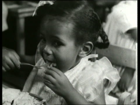 B/W 1930's close up of young black girl eating / nursery school / SOUND