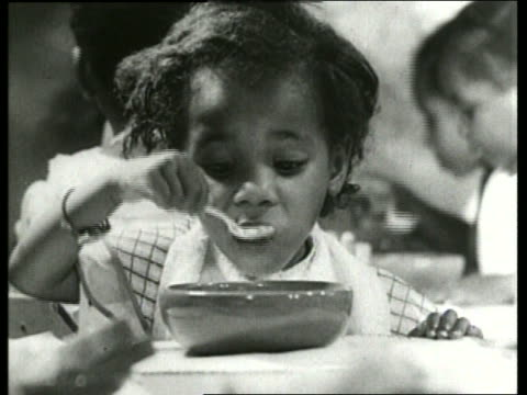 b/w 1930's close up of young black girl eating with spoon / sound - canteen stock videos & royalty-free footage