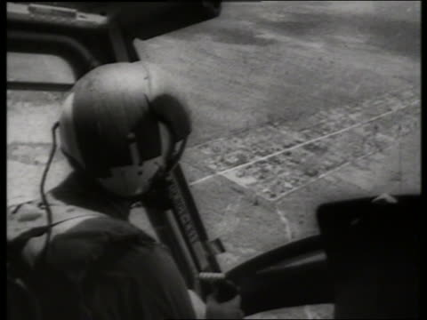 b/w 1960's close up soldier rides in helicopter over countryside / vietnam / sound - pilot stock videos & royalty-free footage