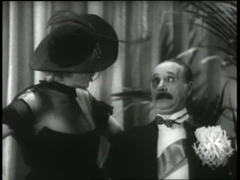 B/W 1930's close up woman yells at man (Ben Turpin), pie hits her in face then pie hits man in face