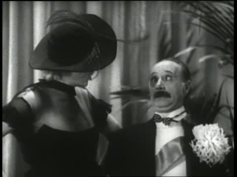 vídeos y material grabado en eventos de stock de b/w 1930's close up woman yells at man (ben turpin), pie hits her in face then pie hits man in face - pastel dulce