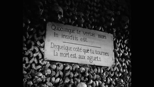 vidéos et rushes de 1950's - close-up of informations sign on wall of catacombs of paris, france - cimetière
