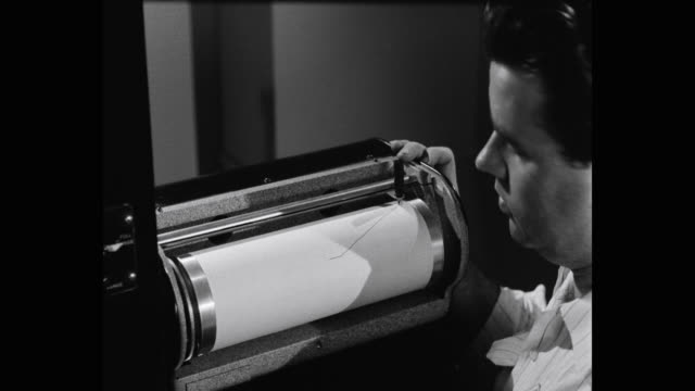 1950's - close-up of man reading graph as measurements are drawn on graph by instrument - measuring stock videos & royalty-free footage