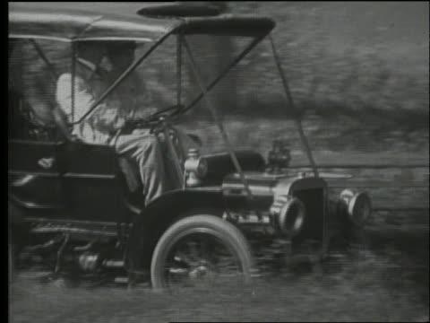 b/w 1900's pan of couple driving early car on country road - 1900~1909年点の映像素材/bロール