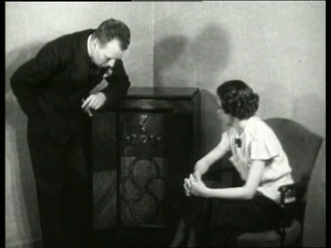 vidéos et rushes de b/w 1930's couple listening to radio in living room / no sound - poste de radio