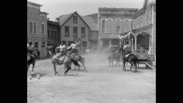 1950's - cowboys on horseback riding into town and firing guns - horse family stock videos & royalty-free footage