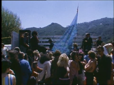 vídeos de stock e filmes b-roll de 1960's crowd of hippies by stage at outdoor concert - love in