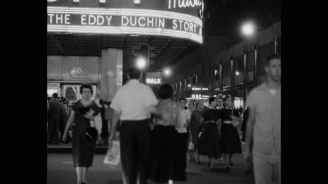 1950's - crowd of people crossing street outside radio city music hall at night, rockefeller center, midtown manhattan, new york city, new york state, usa - radio city music hall stock videos & royalty-free footage