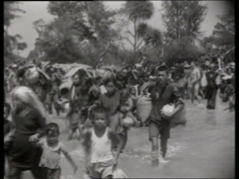 B/W 1960's crowd of Vietnamese walking in water / Vietnam / NO