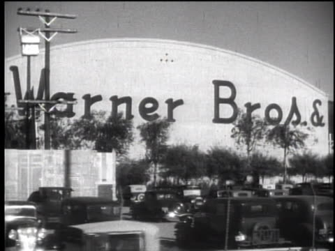 """1930's driver's pov passing warner bros. soundstages,  painted in huge letters - """"home of warner bros. & first national pictures"""" - warner bros stock videos & royalty-free footage"""