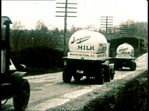 1980 montage 1930's era car and milk trucks on road  - 禁酒法点の映像素材/bロール