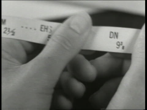 B/W 1930's extreme close up fingers holding ticker tape / Unreal Newsreel