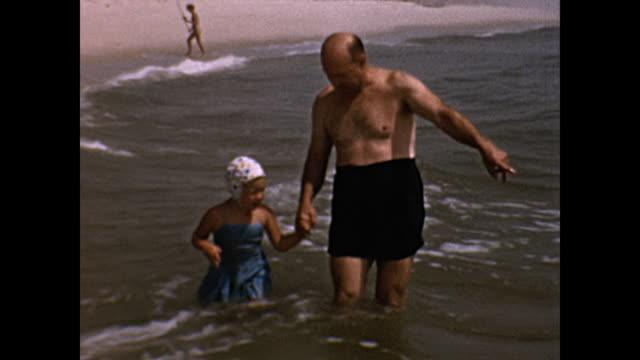 vidéos et rushes de 1950's family at the beach - petit enfant