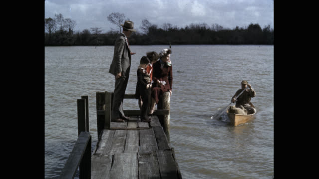 stockvideo's en b-roll-footage met 1950's - family enjoying on wooden pier by river, usa - peddel