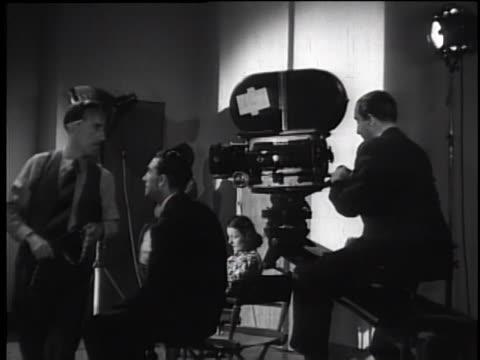 vidéos et rushes de 1930's film set - director reading script and directing scene - décor de cinéma