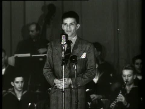 vídeos de stock e filmes b-roll de b/w 1940's frank sinatra talking singing into microphone on stage / no - frank sinatra