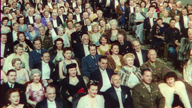 1940's high angle audience in formalwear clapping in theater / The Sun Comes Up