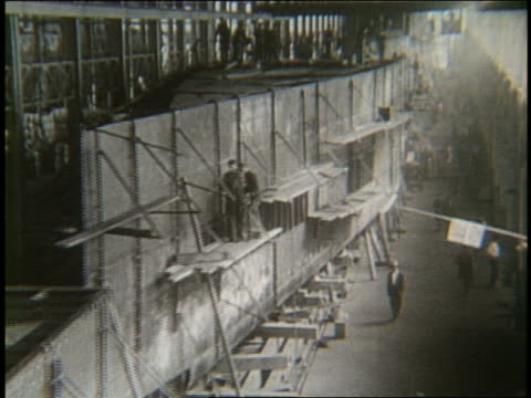 b/w 1900's high angle crane shot thru ship factory - cantiere navale video stock e b–roll