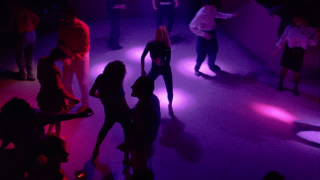 1980's high angle medium shot people dancing under colored lights on dance floor in nightclub