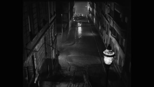1950's - high angle view of cars driving on street at night, paris, france - mysterium bildbanksvideor och videomaterial från bakom kulisserna
