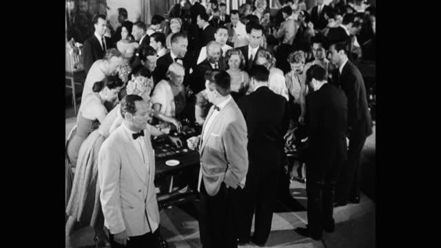 1950's - high angle view of people playing in casino - ルーレット点の映像素材/bロール
