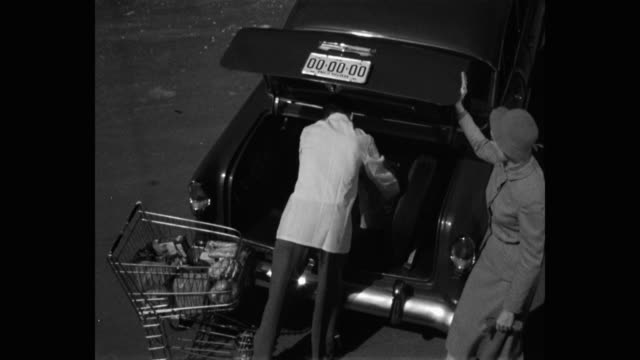 1950's high angle view of store worker loading groceries into woman's car trunk - paper bag stock videos & royalty-free footage