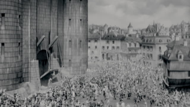 B/W 1700's high angle wide shot crowds storming castle in city / French Revolution / A Tale of Two Cities (1935)