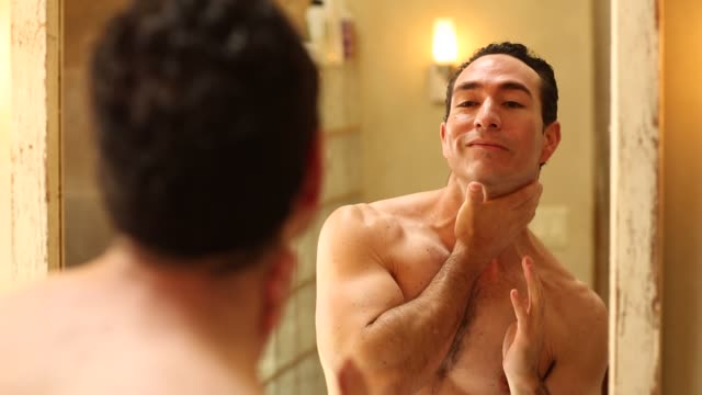 40's hispanic man looking into mirror - contented emotion stock videos & royalty-free footage