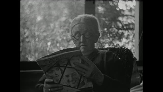 vídeos de stock, filmes e b-roll de 1930's home movie - grandmother reads magazine - óculos de leitura