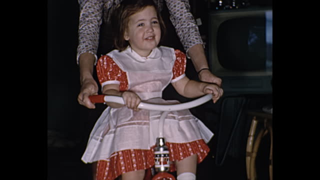 1950's home movie - toddler girl in living room with christmas presents - tricycle stock videos & royalty-free footage