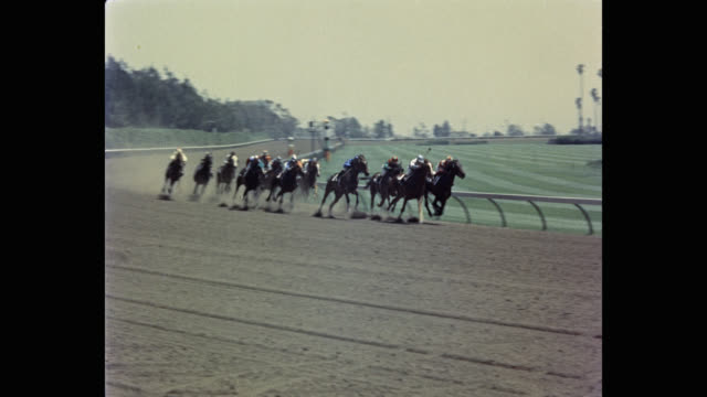1950's - jockeys riding horses , during race, hollywood park racetrack, inglewood, california, usa - pferderennbahn stock-videos und b-roll-filmmaterial