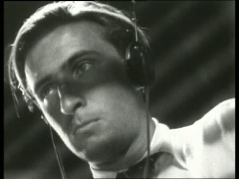 b/w 1930's low angle close up of man wearing headphones / no sound - solo uomini giovani video stock e b–roll