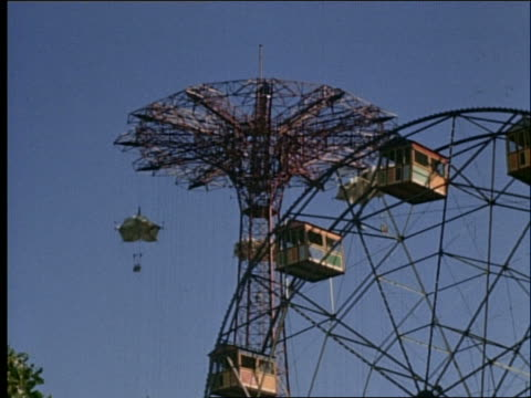 1940's low angle tilt down of parachute ride and ferris wheel / coney island - coney island stock videos and b-roll footage