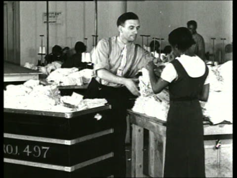 b/w 1930's man and black woman load cart with clothing / sound - 1930 stock videos & royalty-free footage