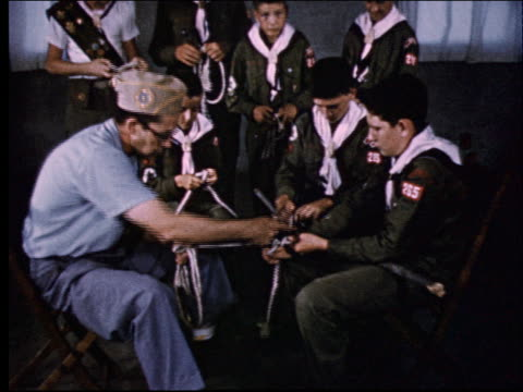 1950's man and boy scouts practice tying knots in ropes - boy scout stock videos & royalty-free footage