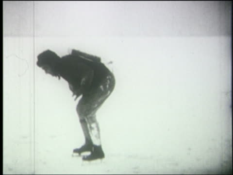 b/w 1920's man on ice skates with jet pack on back falls down on ground - eislaufen stock-videos und b-roll-filmmaterial