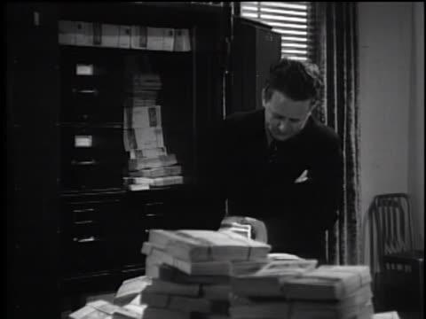 vídeos y material grabado en eventos de stock de 1930's - man putting documents into safe - plató de cine