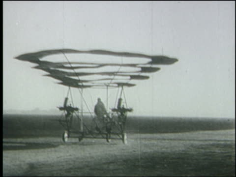 b/w 1930's man riding strange early helicopter on ground away from camera - 発明家点の映像素材/bロール