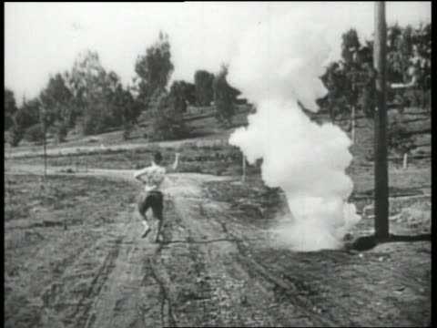 b/w 1920's man running on dirt road with explosions around him - slapstick stock videos & royalty-free footage
