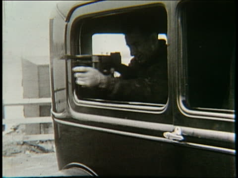 b/w 1920's man shooting machine gun from car window - gun stock videos & royalty-free footage