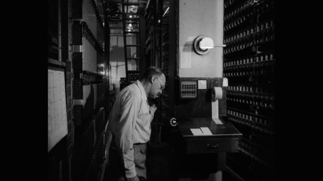 stockvideo's en b-roll-footage met 1950's - man talking on telephone in telephone network control room - regelkamer