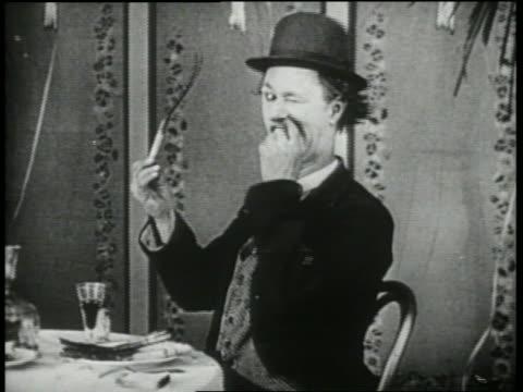B/W 1920's man (Ben Turpin) trying to eat twisting, bending piece of asparagus