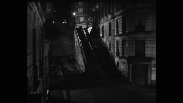 1950's - man walking downstairs at night, paris, france - bianco e nero video stock e b–roll